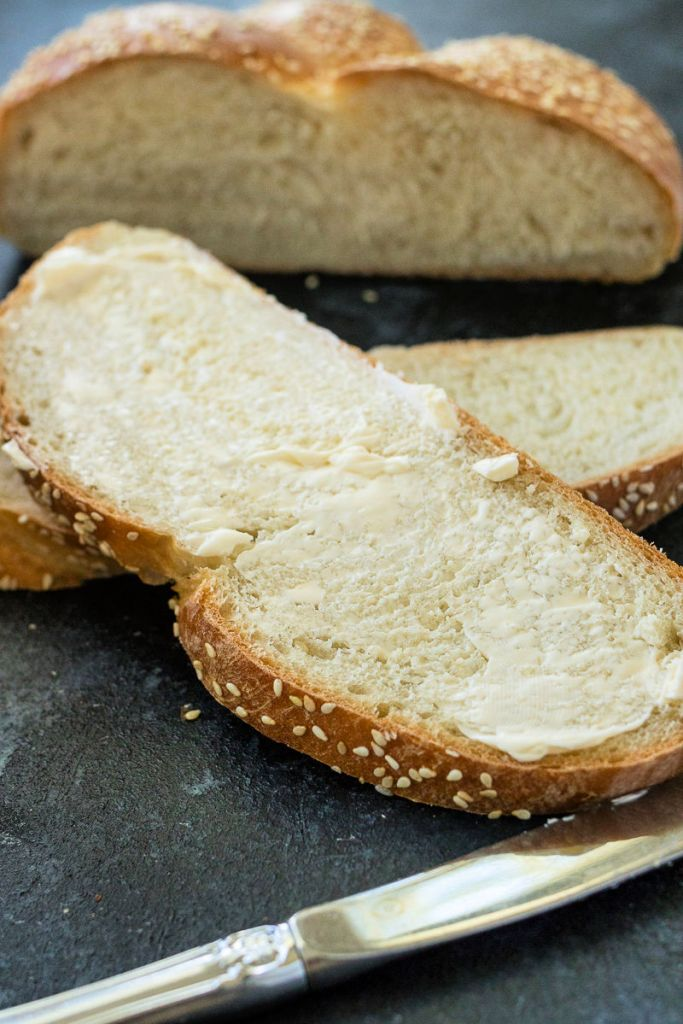 photo of sesame seed braided loaf slices with butter spread on top