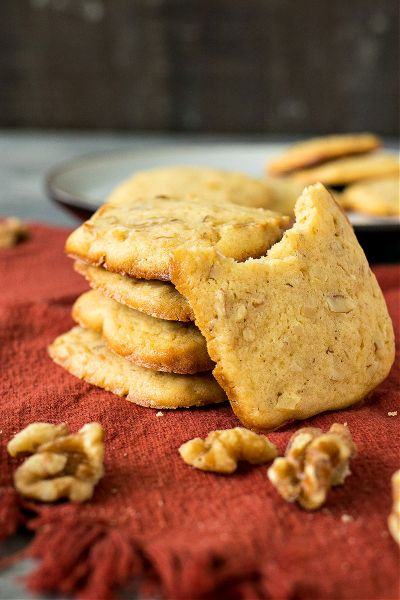 stacked maple walnut cookies on a red orange napkin and one cookie with a bite removed