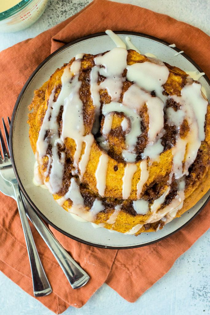 overhead shot of pumpkin cinnamon rolls pancakes stacked on a white plate