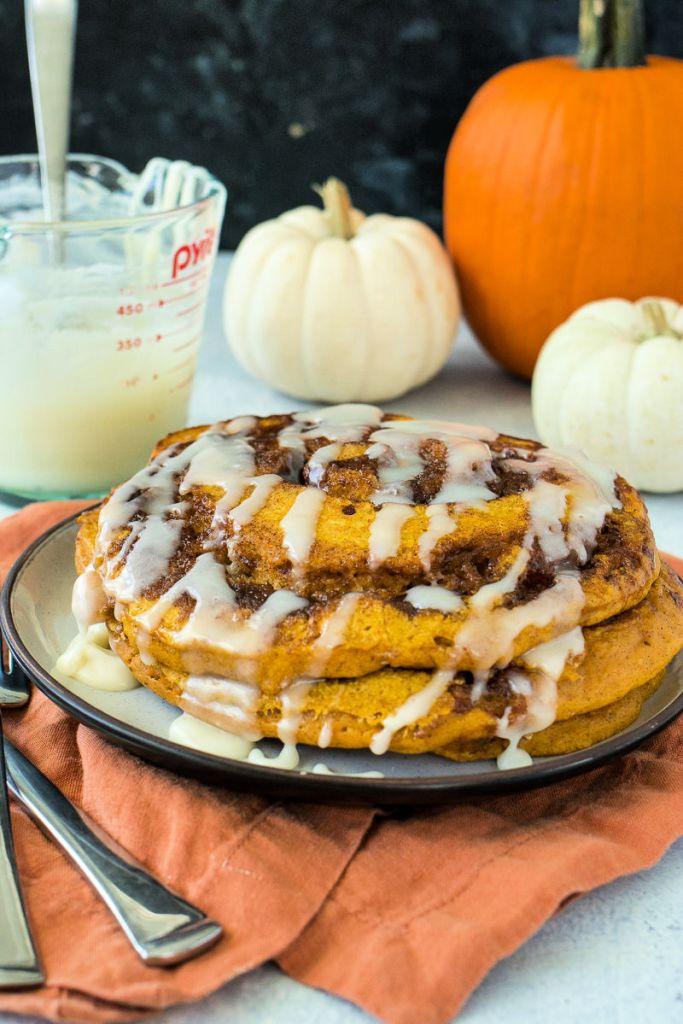 dead on photo of pumpkin cinnamon roll pancakes on a plate