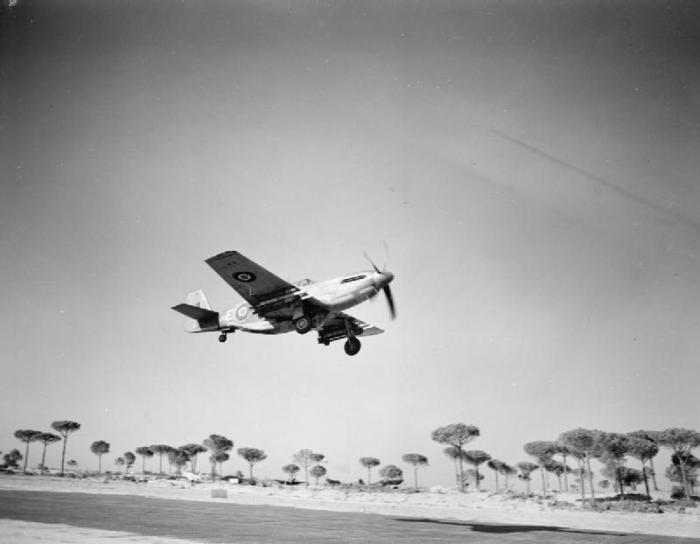 North American Mustang Mark III, del 260° Squadron RAF, decolla dall'aeroporto, armato con otto missili da 3 pollici posti sotto ogni ala. L'ombra dell'aeromobile rispetto al sole è un chiaro segno che il decollo era in direzione Lido di Savio.