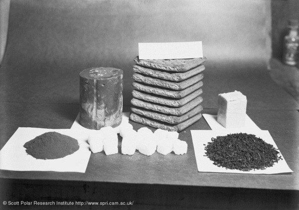 Sledging ration for one man for one day. Rations laid out on a table. British Antarctic Expedition 1910-13 (Ponting Collection).