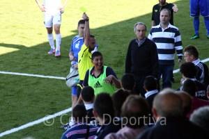 El árbitro amonesta a un jugador del banquillo local delante de Álvaro Pérez