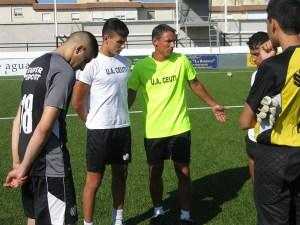 Juanma Alamillos dialoga con algunos jugadores sobre el césped del estadio