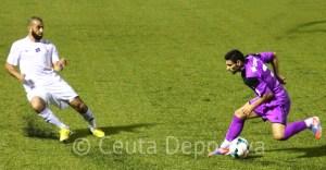 Perita, el jugador más entonado de la AD Ceuta FC, intenta frenar la subida del lateral izquierdo Javi Gallardo