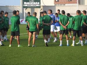 José Antonio Asián habla con sus jugadores sobre el césped del Murube antes del partidillo