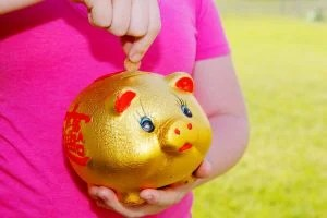 Girl_Purring_Money_Into_Piggy_Bank