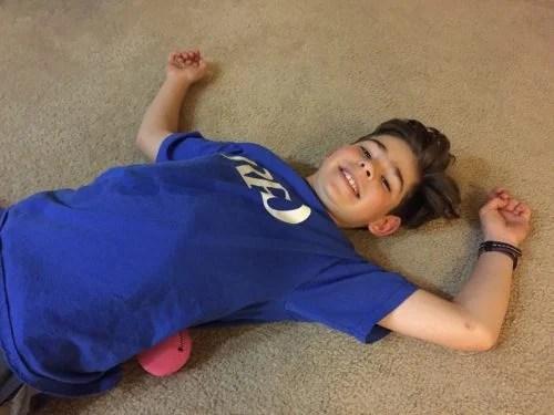 boy lays on worm body roller