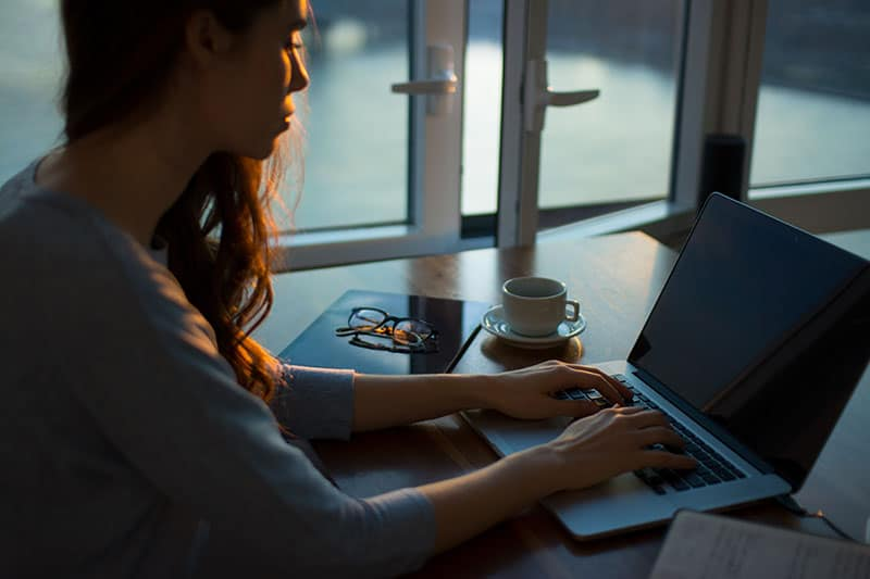 girl on computer at desk working - Tips for Financial Security to Stay Worry-free