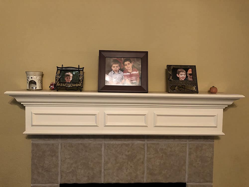 before picture of mantel with photo of the kids from preschool