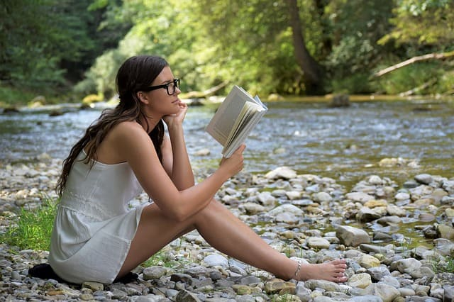 girl reading book outside woman outdoors