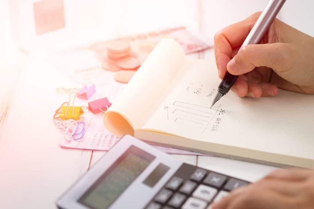 photo-of-person-holding-pen-writing planning budget