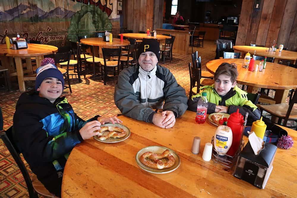 apres ski winter park resort family eating pretzels