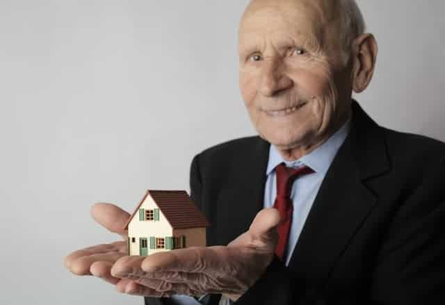 man-in-black-suit-holding-miniature-house-3831828
