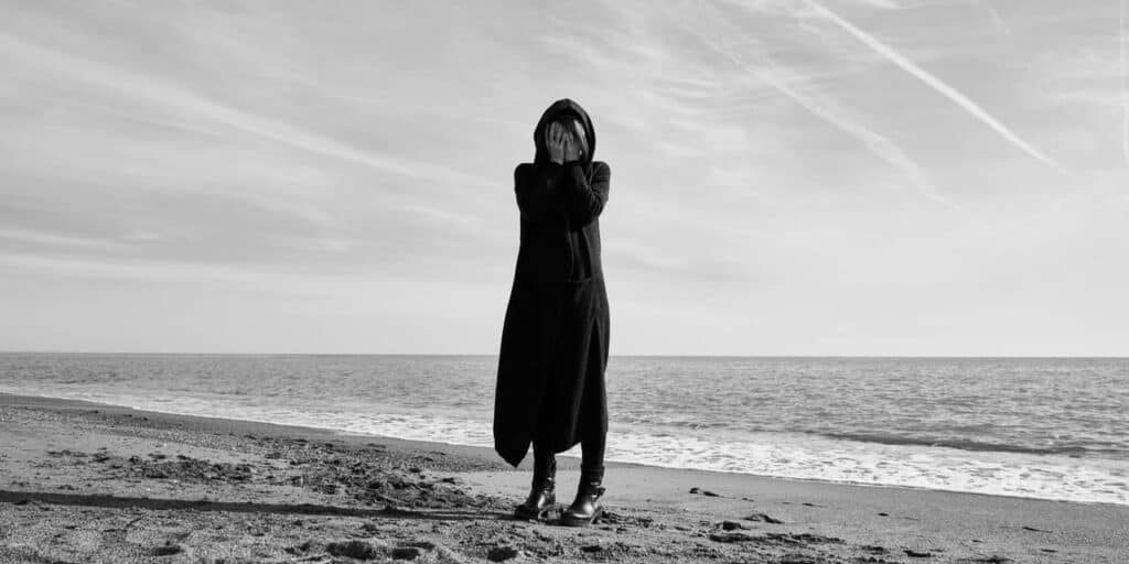 black and white - woman standing at the beach