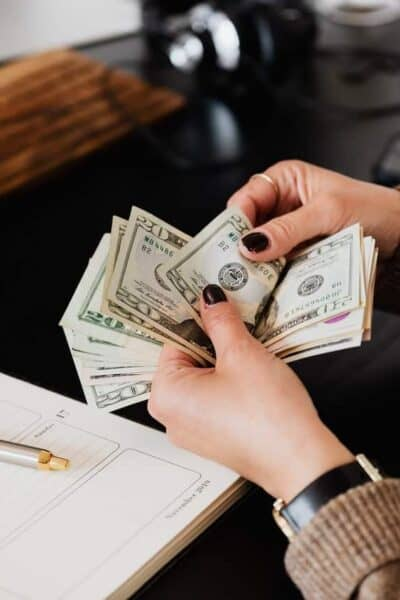 woman-counting-money-at-modern-office-table