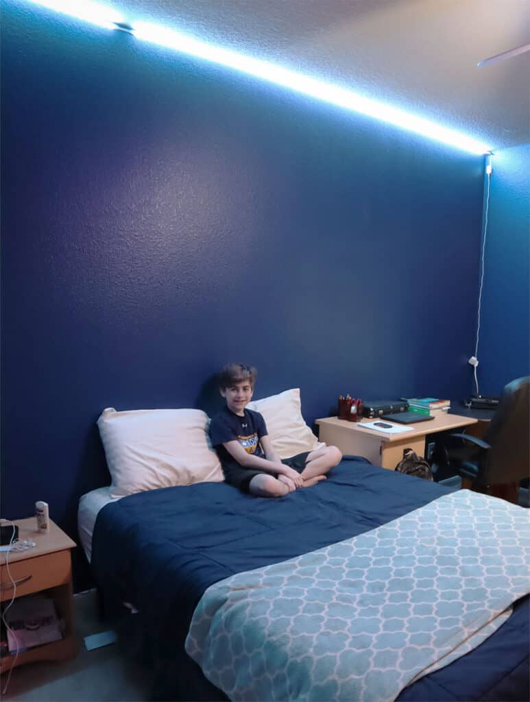 noah pre-teen on bed strip lights in room blue_1