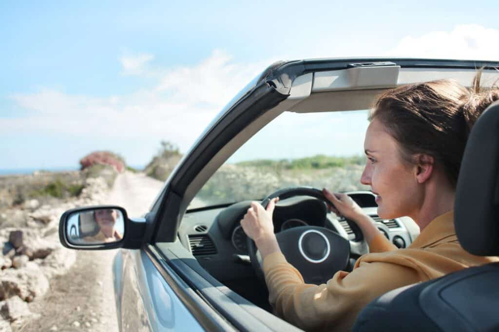 woman driving convertible car in desert