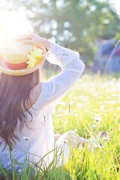 happy woman in hat in field with long hair
