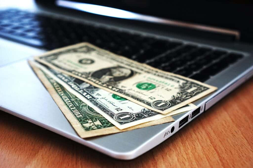 dollar bills money on a laptop computer