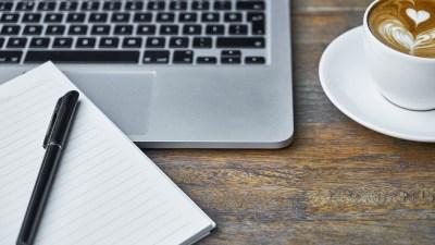 Cursos online con una laptop, un café y una libreta de apuntes