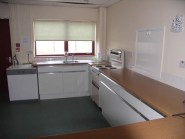 Kitchen with cooker, microwave/, fridge, and hot water urn.