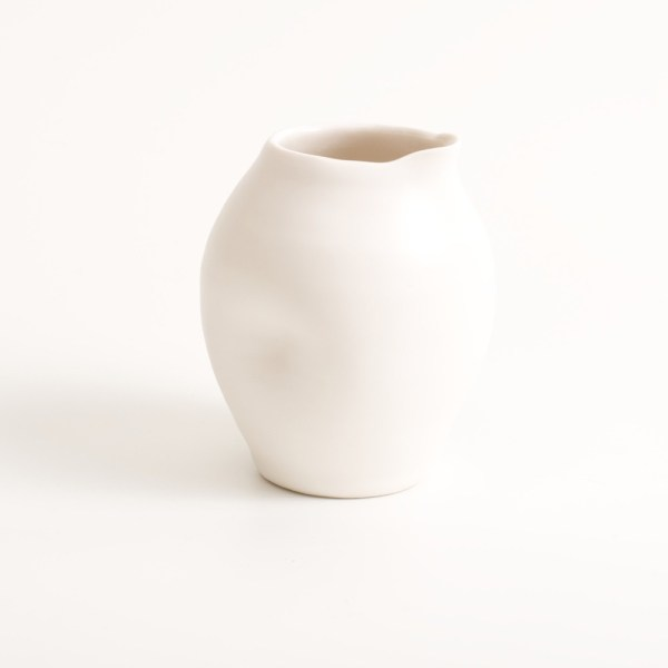 Handmade porcelain dimpled jug small white. With a matt white glaze on the outside and soft coloured inside. Available in white, grey and turquoise, in two sizes. Perfectly formed dimples to fit in your hand. Handmade by Linda Bloomfield in London. Sold on chalkandmoss.com.
