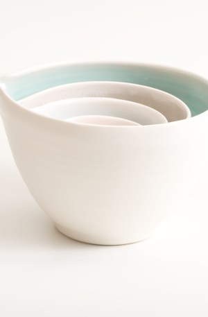 Handmade nesting porcelain pouring pottery bowls by Linda Bloomfield. Set of four. Featuring tactile dimples instead of handles. Inside glazed in pale blue, turquoise, pink or grey. Available as a set of three or four.
