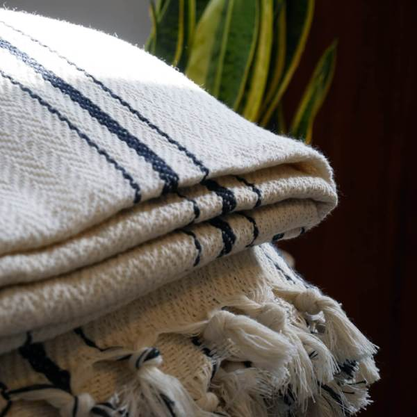 Enes large herringbone blanket for a sofa or bed. Cream with black stripes and fringing. 100% cotton, 240 x 200cm.