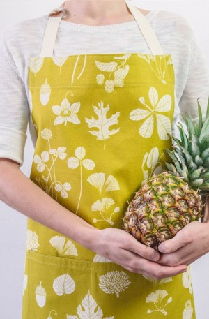Botanical apron made from undyed cotton, and using water based dyes in the screen print. Available in several colours, seen here in chartreuese lime. By Softer + Wild, available on nature connected homeware shop Chalk & Moss.