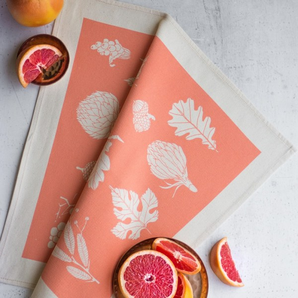 Cotton napkins in a lively winter leaf print - 4 colours available, seen here in fun peach. Designed and made by Softer + Wild, available on Chalk & Moss (chalkandmoss.com).