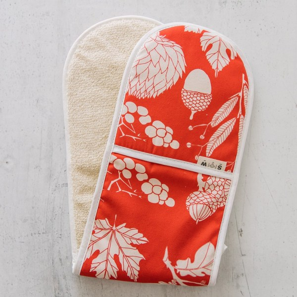 Red oven gloves in a winter leaf design. Padded cotton red double oven gloves designed and hand screen printed in Sussex UK. Part of a botanical kitchen textile range in many vibrant colours, including aprons, tea towels, napkins and oven mitts.