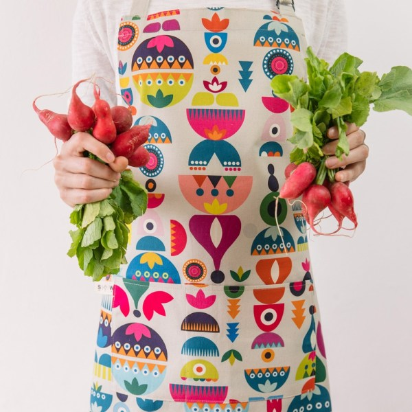 """Cooking apron combining Scandinavian shapes and colours with Eastern European folklore. Inspired by retro Christmas tree baubles. Available in two colours. This is the """"Bright"""" design. 60cm X 80cm."""