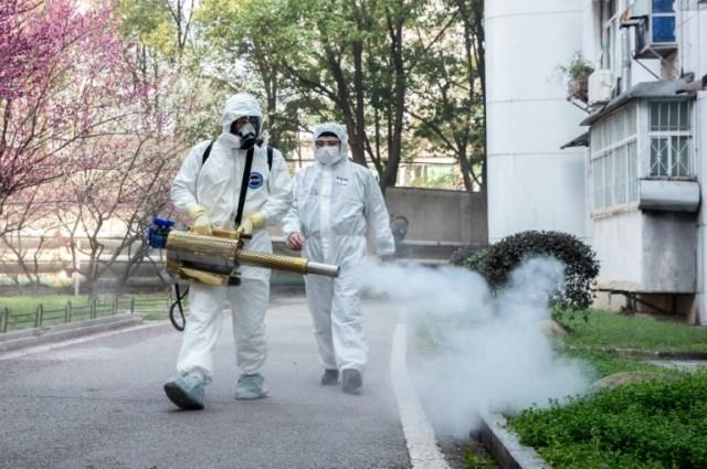 Des bénévoles désinfectent un quartier résidentiel à  Wuhan le 23 février 2020  (AFP - STR)