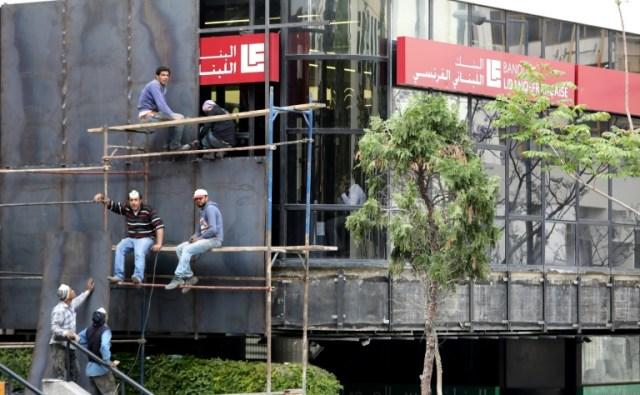 Des ouvriers installent des barrières métalliques devant la façade d'une banque à Beyrouth comme mesure de protection après que des manifestants antigouvernementaux ont saccagé des banques, le 29 avril 2020 (AFP - ANWAR AMRO)