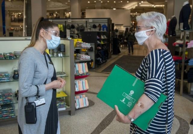 Une employée du magasin Simons explique les mesures de sécurité à une cliente à son arrivée au magasin, à Montréal, Canada, le 25 mai 2020 (AFP - Sebastien St-Jean)