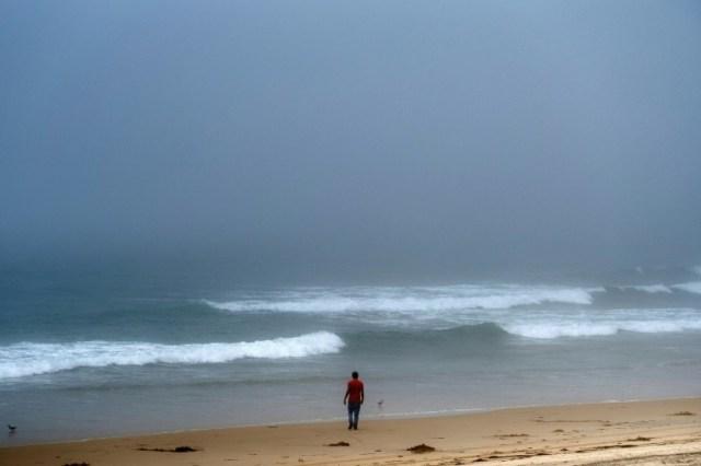 Un homme marche sur la plage de Tijuana, Etat de Baja California state, Mexique, le 2 ao^t 2020  (AFP - Guillermo Arias)