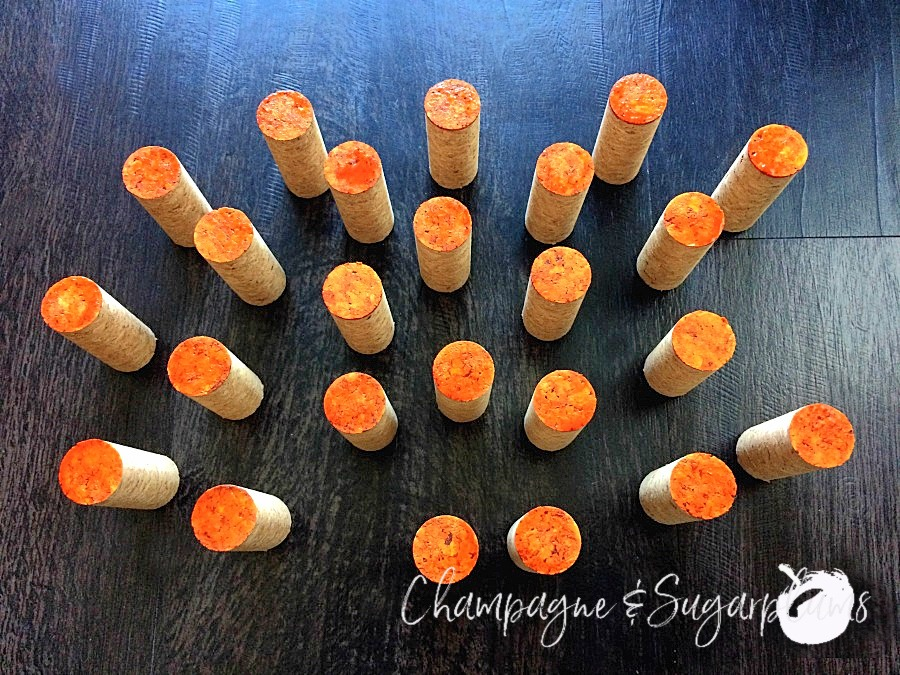 Corks with the tops painted orange by Champagne and Sugarplums