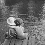 two children sitting on a jetty black and white