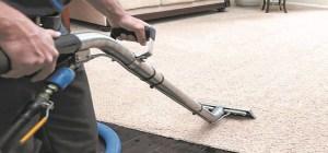 A man steam cleaning a carpet