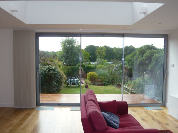 fully stacked back onto the left hand wall adjacent to the patio doors: large sliding patio doors