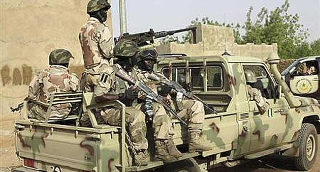 A file photo of Nigerian soldiers sitting on a military pick-up truck at a military base.