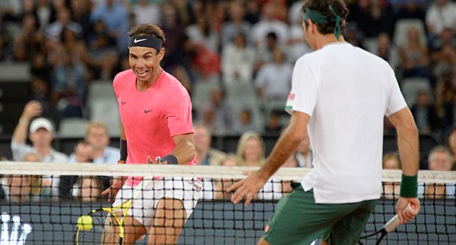 Spain's Rafael Nadal (L) plays a return to Switzerland's Roger Federer (R) during their tennis match at The Match in Africa at the Cape Town Stadium, in Cape Town on February 7, 2020. RODGER BOSCH / AFP