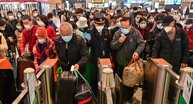 People wearing face masks as a preventive measure against the COVID-19 novel coronavirus walk to a train, one of the stops being Wuhan, at a station in Shanghai on March 28, 2020.