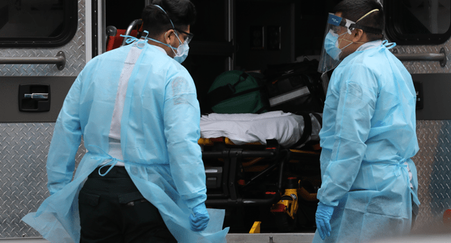 Medics wear protective gear as they arrive at a Brooklyn hospital to pick up a patient on April 18, 2020 in the Brooklyn borough of New York City.   Spencer Platt/Getty Images/AFP