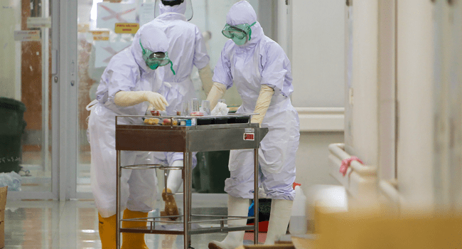 Hospital kitchen workers clad in full PPE deliver meals to COVID-19 coronavirus patients at an isolation section of Bogor general hospital in Bogor, West Java on April 23, 2020. ADITYA AJI / AFP