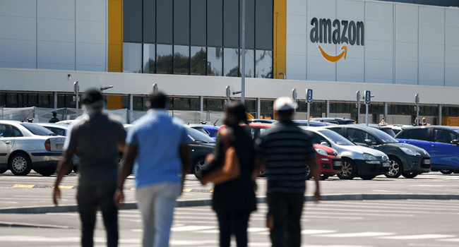 Amazon workers arrive at the company's centre in Bretigny-sur-Orge on May 19, 2020 as Amazon France partially reopens amid the pandemic of the novel coronavirus (COVID-19). Eric PIERMONT / AFP