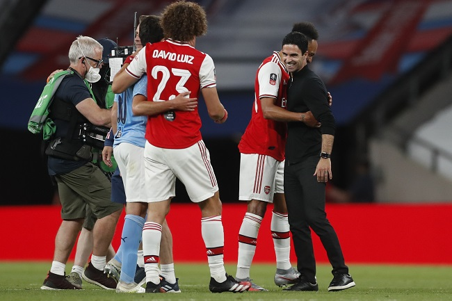 Arsenal's Spanish head coach Mikel Arteta (R) embraces Arsenal's Gabonese striker Pierre-Emerick Aubameyang (2R) at the end of the English FA Cup semi-final football match between Arsenal and Manchester City at Wembley Stadium in London, on July 18, 2020. (Photo by MATTHEW CHILDS / POOL / AFP) / NOT FOR MARKETING OR ADVERTISING USE / RESTRICTED TO EDITORIAL USE
