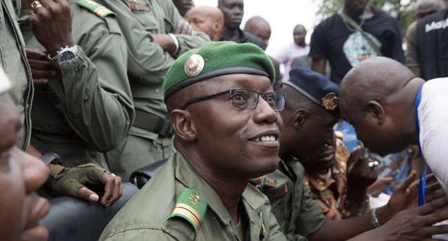 Colonel Malick Diaw (C), vice-president of the CNSP (National Committee for the Salvation of the People) smiles at a crowd of supporters as he arrives escorted by Malian soldiers at the Independence square in Bamako, on August 21, 2020. ANNIE RISEMBERG / AFP