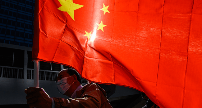 A pro-Beijing supporter holds China's national flag as he and others gather outside the Legislative Council in Hong Kong on November 12, 2020, a day after the city's pro-Beijing authorities ousted four pro-democracy lawmakers. Anthony WALLACE / AFP